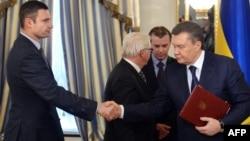 Лидер оппозиции Виталий Кличко (слева) пожимает руку президенту Виктору Януковичу после подписания соглашения о перемирии. Киев, 21 февраля 2014 года.
