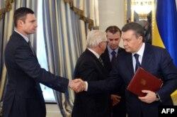 УДАР партиясы жетекшісі Виталий Кличко оппозиция мен билік арасындағы келісімге қол қойғаннан кейін Виктор Януковичтің қолын алып тұр. Киев, 21 ақпан 2014 жыл.