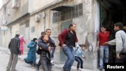Banorët përpiqen të strehohen pas një sulmi të mëparshëm në Siri