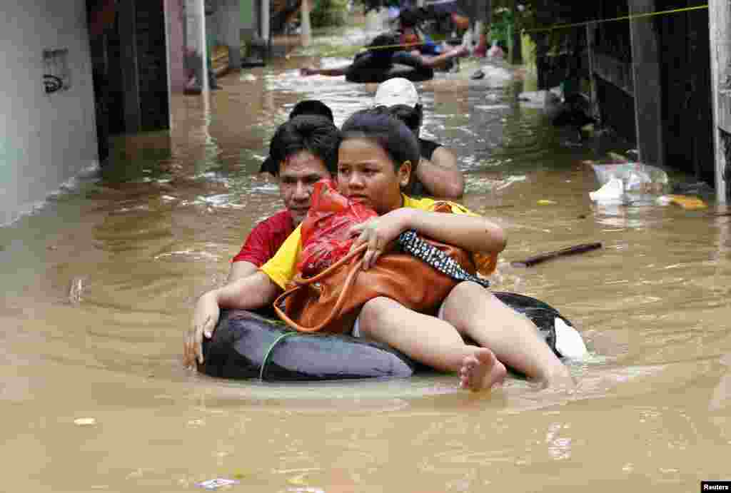 A woman sits on a rubber float as she is evacuated from her flooded housing complex in Jakarta, Indonesia. Floods inundated several areas of Jakarta due to the overflow of the Ciliwung River and several days of heavy rains. (Reuters/Enny Nuraheni)