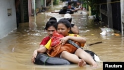 A woman sits on an inflatable rubber tube as she is evacuated from her flooded housing complex in Jakarta on January 16.