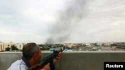 Libya -- A rebel fighter takes cover atop a building during a firefight and shelling near Tripoli street in Misurata, 21Apr2011