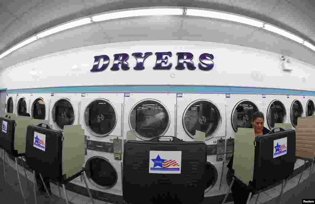 A voter casts her ballot inside a laundromat in Chicago, Illinois.