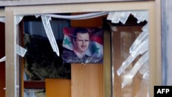Фотография сирийского президента Башара Асада сквозь разбитое стекло в здании после взрыва смертника. Дамаск, 9 февраля 2016 года. Иллюстративное фото.