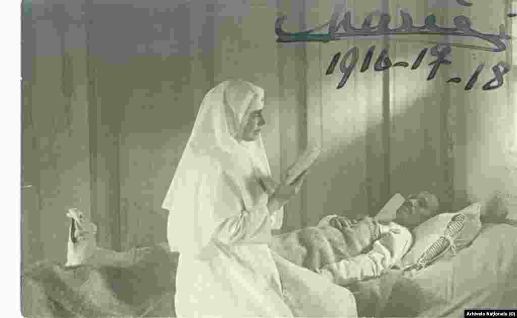 Maria încurajează un soldat rănit. Carte poștală cu semnătura Reginei, 1917-1918. Imaginile suveranilor Unirii pe cele două embleme care decorează Arcul de Triumf din București sunt cele din acești ani: Regele-soldat și Regina-soră medicală.