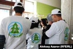 """Молодые люди в футболках с надписью """"Я за Кок-Жайляу"""" (то есть за курорт) собрались и слушают женщину в костюме перед началом слушаний. Алматы, 25 февраля 2014 года."""