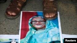 Протестувальник стоїть на портреті прем'єра Бангладеш Шейх Хасіни