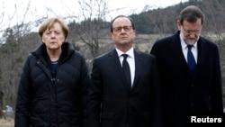 Германия канцлери Ангела Меркел (чапда), Франция президенти Франсуа Олланд (ўртада) ва испания бош вазири Мариано Ражой учоқ қулаган ҳудудда.