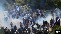 Протестувальники тримають прапор Греції під час сутичок з поліцією неподалік Пісодері, 17 червня 2018