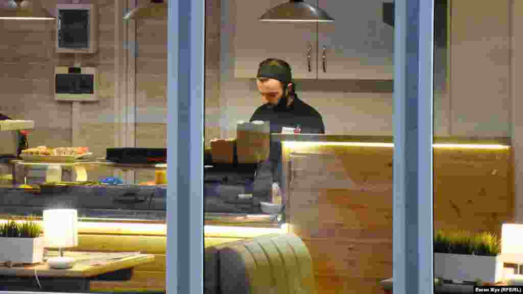 Продавець упаковує суші, маска – на підборідді