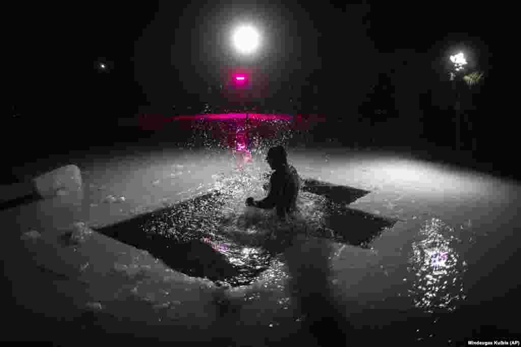 Литовський православний купається у крижаній воді невдовзі після опівночі в озері неподалік литовської столиці Вільнюса