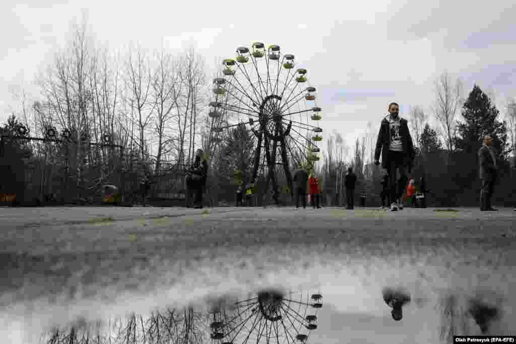 Людзі гуляюць каля кола агляду ў бязьлюдным горадзе Прыпяць каля Чарнобылю ва Украіне. 26 красавіка адзначаецца 35-я гадавіна Чарнобыльскай трагедыі. (epa-EFE/Oleg Petrasyuk)