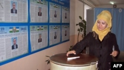 Uzbekistan -- A woman casts her ballot at a polling station in Tashkent, March 29, 2015