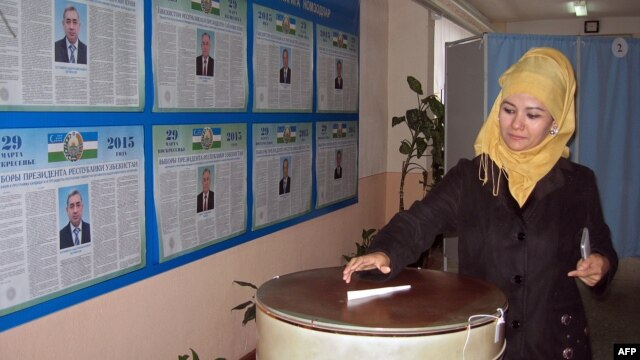 A woman casts her ballot at a polling station in Tashkent on March 29.