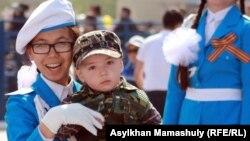 Школьница с маленьким мальчиком в день празднования победы во Второй мировой войне. Актау, 9 мая 2012 года. Иллюстративное фото.
