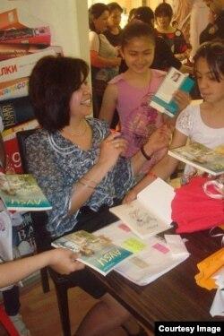 Rehan Yusifqızı Şıxlınskaya uşaqlar üçün öz kitabını imzalayır.