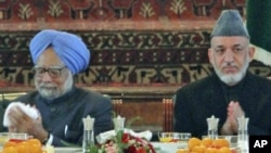 Afghan President Hamid Karzai (right) and Indian Prime Minister Manmohan Singh eat lunch at the presidential palace in Kabul.