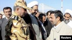 İranın prezidenti Mahmud Ahmadinejad (sağda) ordunun yüksək rütbəli rəhbərlərindən biri ilə Cahar Mahalda hava limanında görüşür. 9 noyabr 2011
