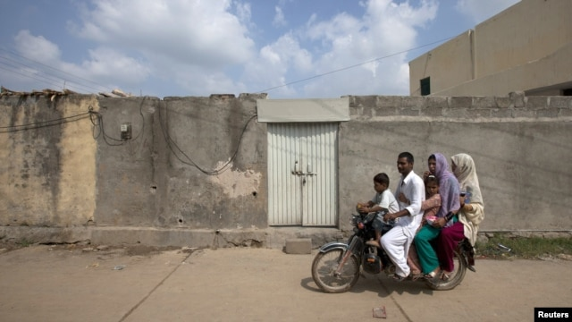 A family rides past the locked house of a Christian girl accused of blasphemy, on the outskirts of Islamabad.
