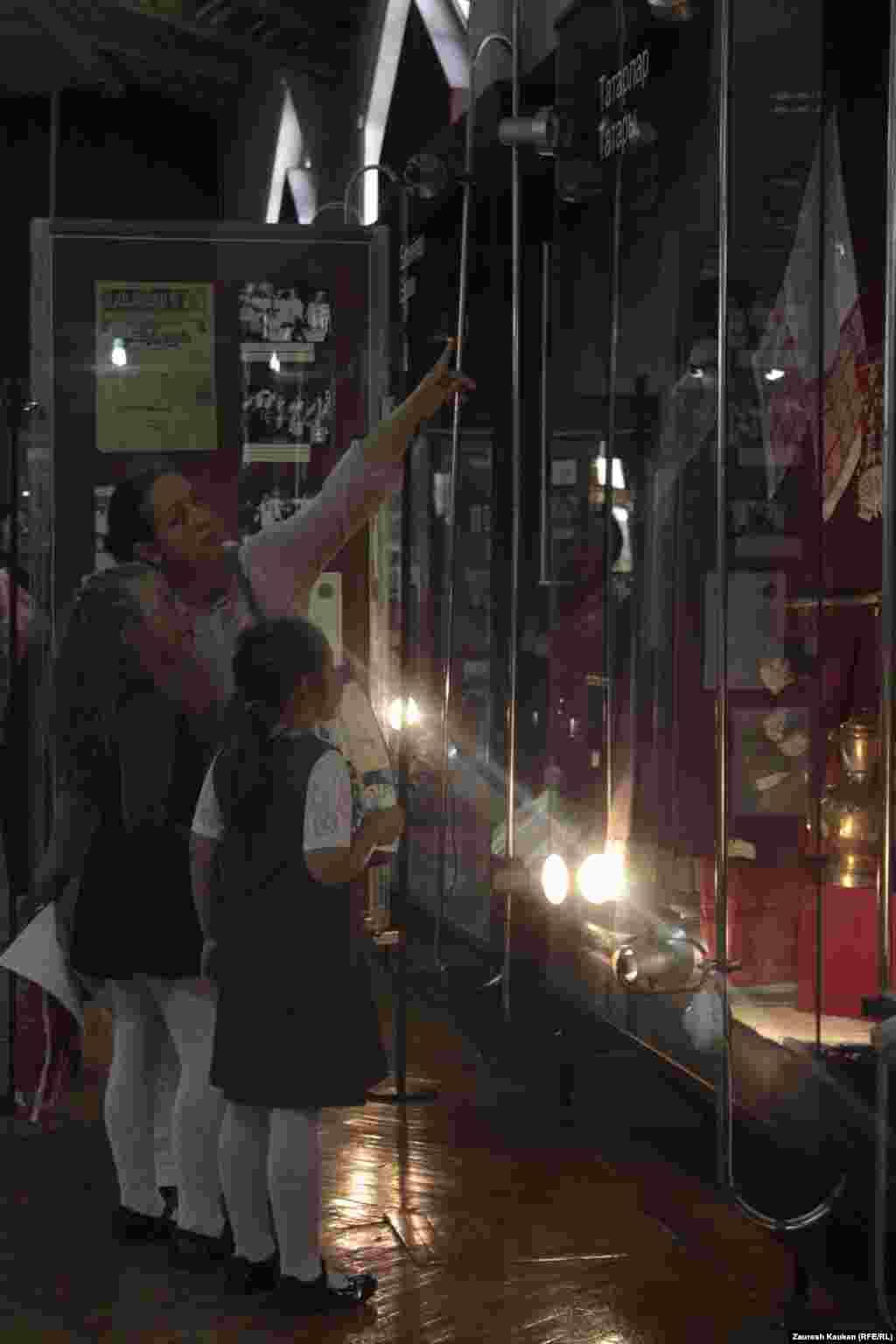 Эта посетительница акции показывает своим дочерям экспонаты выставки о жизни татарской общины.