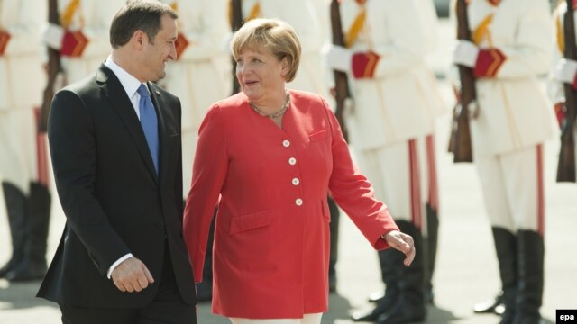 Moldovan Prime Minister Vlad Filat (left) walks with German Chancellor Angela Merkel during a welcoming ceremony at Chisinau airport.