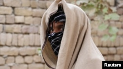 "A nineteen-year-old Taliban deserter hides his face in Kunduz Province. ""I faced the darkest moment of my life seeing my brother's body covered with blood and dust,"" he said."