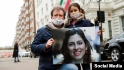 Nazanin Zaghari-Ratcliffe's husband, Richard Ratcliffe, and her daughter pose with a picture of her in London.