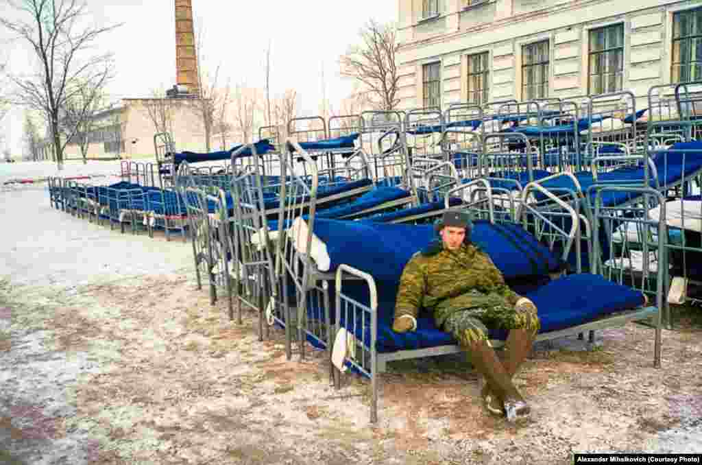 A soldier guards his bed, which he dragged outside during a fire alarm.