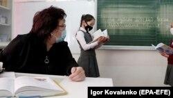 Школьницы носят защитные маски во время урока в день возобновления занятий в начальных классах в центре Бишкека, 9 марта 2021 года.