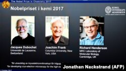A screen displays portraits of winners of the 2017 Nobel Prize in chemistry, Jacques Dubochet (left to right), Joachim Frank, and Richard Henderson, at the Royal Swedish Academy of Sciences in Stockholm on October 4.