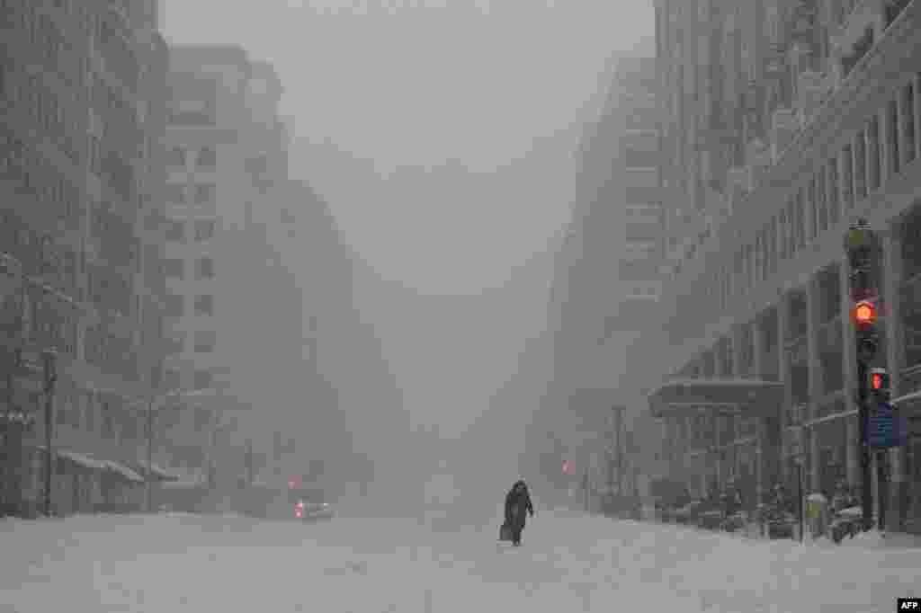 Жінка йде 13-ю вулицею в Нью-Йорку, де припинили рух громадського транспорту через потужний сніговий шторм