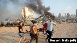 Луѓе носат жртва од местото на експлозијата што го зафати пристаништето во Бејрут, Либан, 04.08.2020.