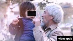 ИМ видеосында өзін Әбу Әмина деп таныстырған ер адам кішкентай баланы көтеріп тұр.