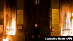 Российский художник-акционист Петр Павленский на фоне горящего здания Банка Франции.