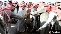 Mourners bury the body of Saudi King Abdullah during his funeral in Riyadh on January 23.
