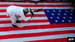 An activist of Jamaat-ud-Dawa, a religious charity founded by Hafiz Mohammad Saeed, beats a U.S. flag with his shoes during a protest rally in Karachi on April 6.