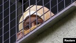 Женщина-мигрант смотрит из окна в центре для беженцев Бела-Езова. Ноябрь 2015 года.