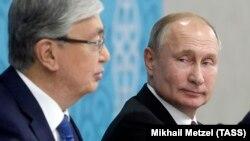 Russian President Vladimir Putin glances at Kazakh President Qasym-Zhomart Toqaev at a session of the 16th Russia-Kazakhstan Interregional Cooperation Forum in Omsk on November 7, 2019.