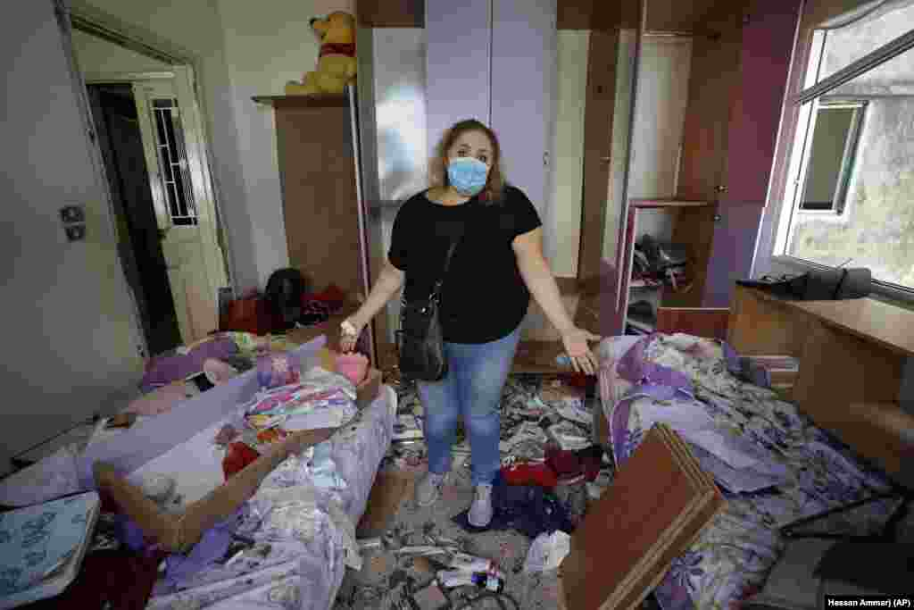 Mona Al Chami, poses for a photograph inside her destroyed apartment after Tuesday's explosion in the seaport of Beirut, Lebanon, Thursday, Aug. 6, 2020.