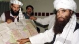 FILE: Jalaluddin Haqqani (R) points to a map of Afghanistan during a visit to Islamabad in October 2001.
