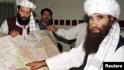 Jalaluddin Haqqani (right), the Taliban's minister for tribal affairs, points to a map of Afghanistan as his son Nasiruddin looks on during a visit to Islamabad, Pakistan, in October 2001.