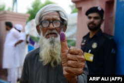 An elderly Pakistani man shows his inked thumb after casting his vote outside a polling station during general elections in Lahore.