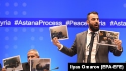 Member of Syrian armed opposition, former officer of the Syrian army, now an opposition, Yasir Abdur Rakhim (R) speaks as he demonstrates photo documents, during a press conference after the seventh round of talks on the Syrian conflict.