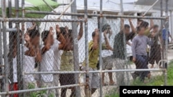 Asylum seekers stand behind a fence at the Manus Island detention centre in Papua New Guinea. There are currently 916 refugees and asylum seekers in the Australian-run facility
