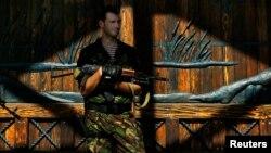 Пророссийский вооруженный сепаратист стоит у ворот дома украинского олигарха Рината Ахметова. Донецк, 25 мая 2014 года.
