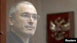 Former oil tycoon Mikhail Khodorkovsky stands behind a glass wall before the start of a court session in Moscow, in October 2010.