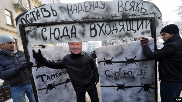 "A young activist wearing a mask of Ukrainian President Viktor Yanukovych invites passersby to go through a symbolic gate with the words ""Customs Union"" and ""Abandon Hope, All Ye Who Enter Here,"" during a protest in front of the presidential office in Kyiv in December."