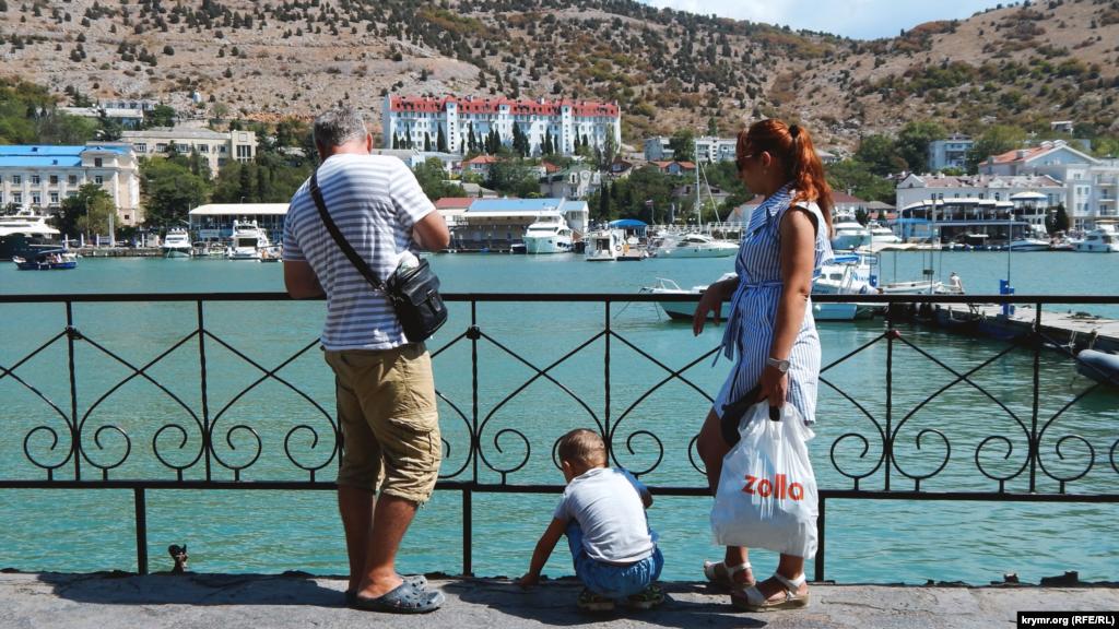 Семья отдыхающих на берегу Балаклавской бухты