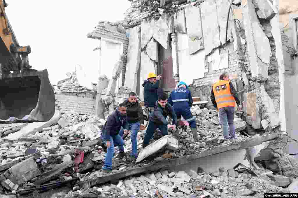 Emergency workers clear debris at a damaged building in Thumane, 34 kilometers northwest of the capital, Tirana.