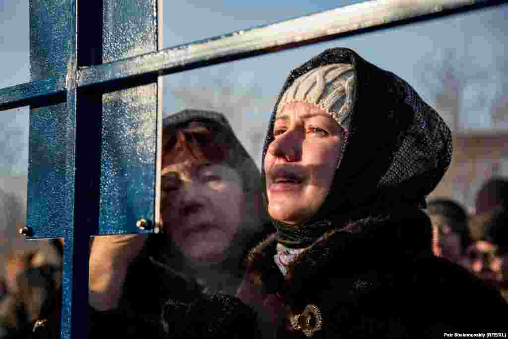 The widow of miner Vitaliy Nezhelskiy cries in front of a memorial.